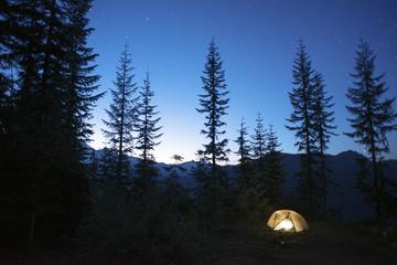 Illuminated tent on silhouette mountain at night
