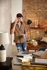 Young man talking on mobilephone at home