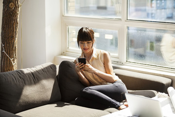 Businesswoman using smart phone while sitting on sofa in office