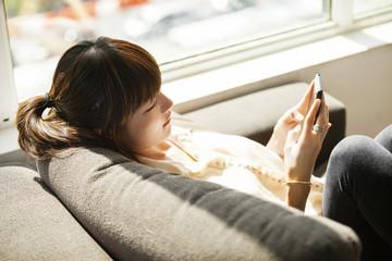 Businesswoman using smart phone on sofa