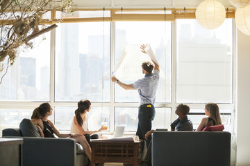 Businessman holding blueprint against window at meeting