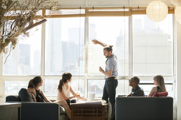 Young businessman showing blueprint in office