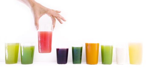 Cropped image of woman holding fresh juice glass against white wall