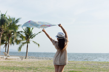 woman on the beach with scarf blowing with wind on white dress and hat