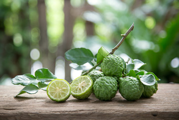 Kaffir lime with leaves on wooden background.