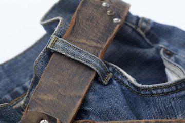 Blue jeans and leather belt on white background.