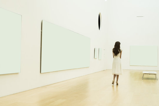 Young woman is looking at the painting in the museum