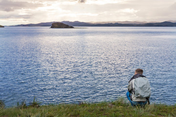 Traveler squatting is enjoying the sunrise
