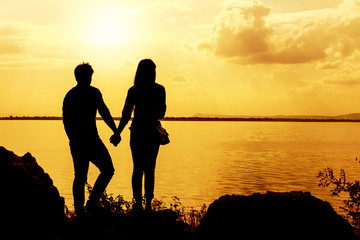 Silhouettes of man and woman holding hands while at sunset