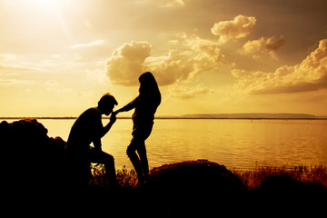 Silhouettes of man and woman kissing hand while at sunset