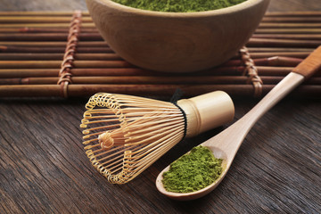 Bamboo whisk and spoon with powdered matcha tea, closeup