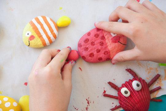 Child making a painted stone fish craft