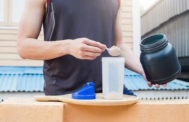 Whey protein, healthy lifestyle, man pour whey powder on the bot