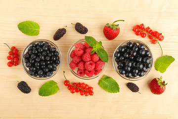 Berries in glass bowl on wooden background