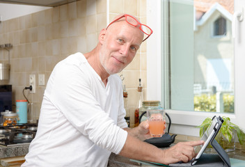 senior man in kitchen using  tablet