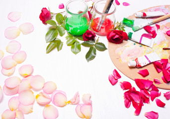 Paints and brushes with rose petals.Workplace of artist,designer