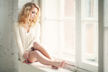 Beautiful Woman with Blonde Looking out the Window
