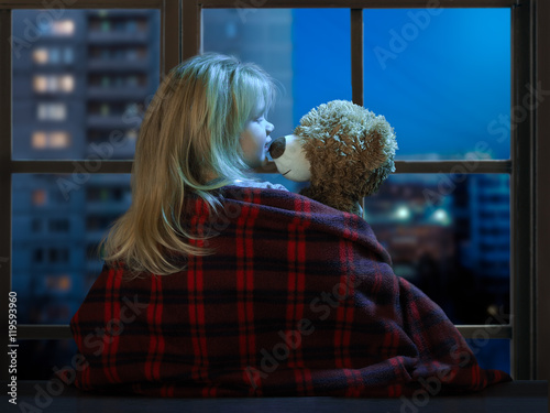 Little girl talking with a toy bear in the window. Outside, the city, home, night