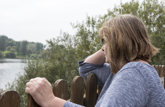 Portrait image of a mature woman resting on a fence, looking out at a view of a lake on an overcast day.