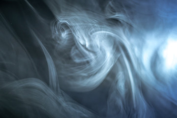 The stream of thick smoke on a dark background