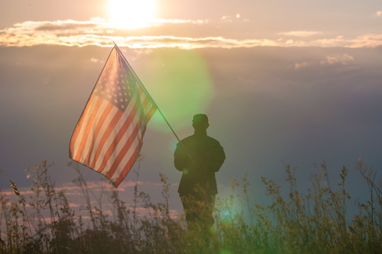 The military stand on the background of sunset with the American flag