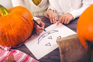Mother with daughter creating big orange pumpkin, close up drawing