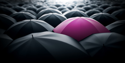 Pink umbrella sticking out of the crowd, women power concept representation