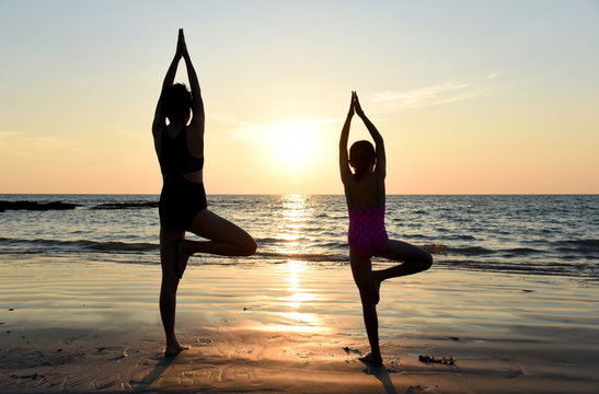 Yoga vrikshasana tree pose by mom and daughter in silhouette with sunset sky background