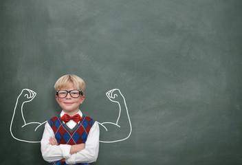 Kind mit Muskeln vor Tafel