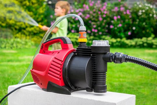 Modern water pump in garden on hot summer day