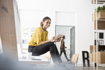Smiling woman sitting on office desk using digital tablet