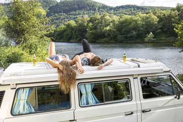 Young couple lying on roof of a van at lakeside