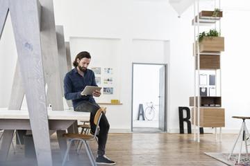 Man sitting on office desk using digital tablet