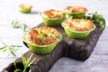Savory cheddar cheese and leek mini quiches with thyme on dark wooden cutting board