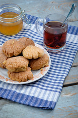 Tea, honey and honey cookies on wooden table