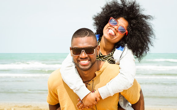Young afro american couple playing piggyback ride on beach - Cheerful african friends having fun at day with blue ocean background - Concept of lovers happy moments on summer holiday - Vintage filter