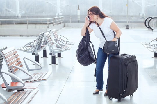 stressed troubled woman in the airport with plenty of bags and luggage