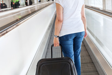 passenger with suitcase luggage on travelator in airport
