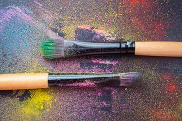 Косметическая кисточка для нанесения макияжа лежит на черном фоне с рассыпанными тенями для глаз