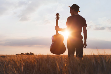 silhouette of musician with guitar at sunset field