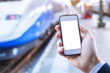 hand holding smartphone with empty blank screen in train station
