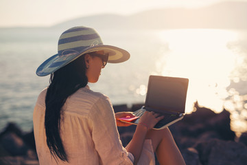 Tourist woman on holidays enjoying online with a laptop on the b