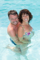 Lovely and happy middle-aged couple in a swimming pool