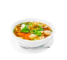 Hot and spicy Thai Dishes. A savoury thick soup made with squid rings, spices and vegetables and crushed peanuts isolated on white background. Selective focus