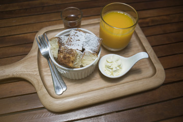 close up toast in a cup with icing sugar powdered on top, honey in a mug shot and orange juice in a glass, put on wooden plate,wooden table,morning breakfast,honey toast menu