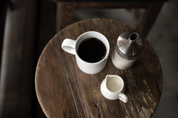 Americana with milk and sugar, coffee on a wooden little table