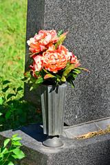 Kunstblumen in einer Vase am Grabstein