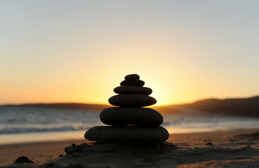 Zen stones on the sand at sunset