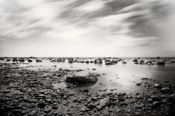 Pebbled beach with dramatic sky, black and white