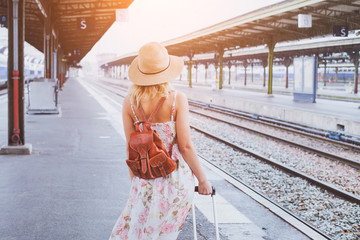 summer travel, woman with suitcase waiting for  her train on platform of railway station